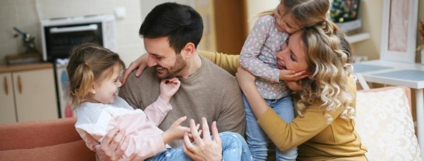 Vader, moeder en twee jonge dochters aan het stoeien